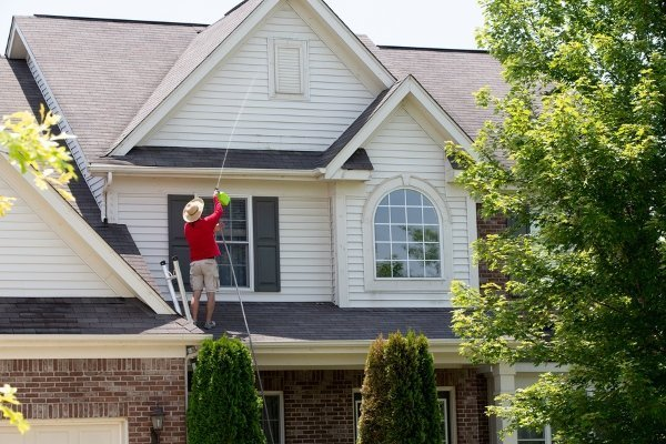 man working on top of roof shingles