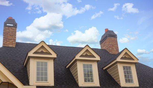three brown painted dormer windows against dark grey asphalt roof