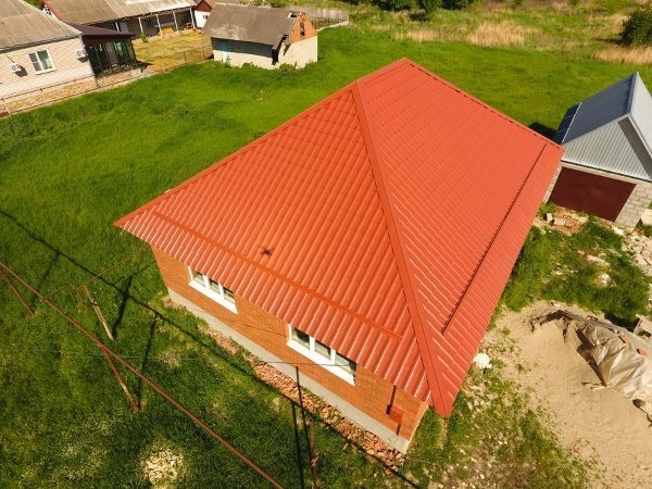 dark orange hipped roof of one story house with orange walls