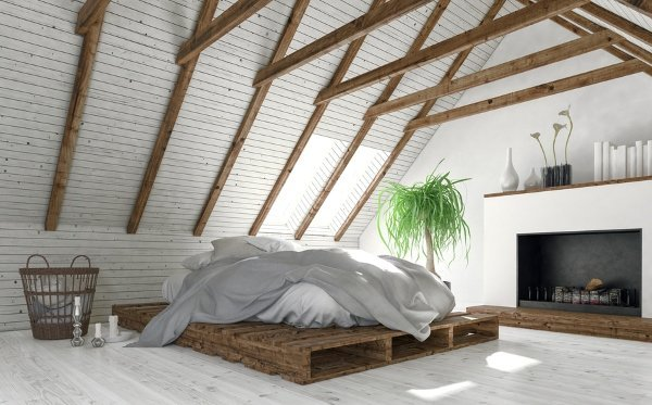 white and clean attic room with bed and fireplace
