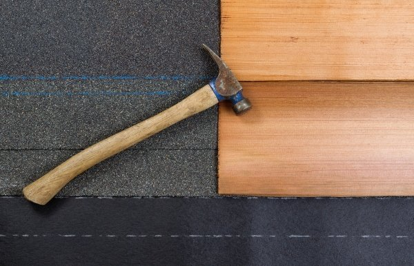 close up view of two wood shingles on roof felt with hammer