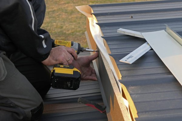 Man using an electric drill to fasten a metal roof.